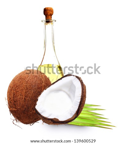 Coconut with oil, milk and palm leaves isolated on white. - stock photo