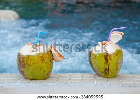 Coconut with straws to drink on the side of the pool - stock photo