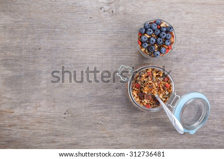 Coconut yogurt topped with grain free muesli made with mixed nuts, seeds, raisins, with blueberries on the top, above view - stock photo