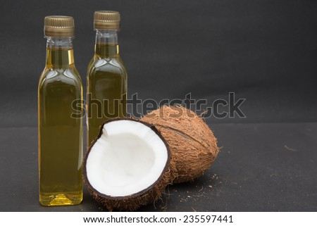 Coconuts cut in half and whole coconuts. Two bottles of coconut oil.
