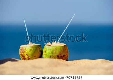 Coconuts with drinking straw on the sand at the sea - stock photo