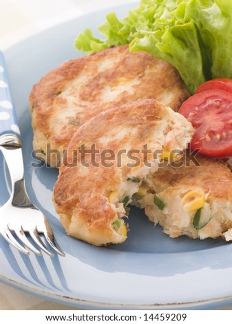 Cod and Salmon Fish Cakes with Corn and Salad - stock photo