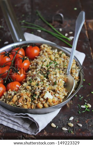 Cod fillet crumble with sesame seeds, sunflower seeds, flax seeds, pine nuts and fresh chopped chives with roasted cherry tomatoes in a pan