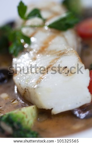 Cod fillet with vegetables and sauce - stock photo