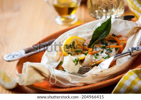 Cod fillets  baked in parchment paper - stock photo
