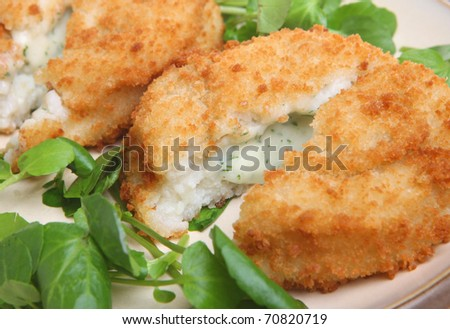 Cod fishcakes with parsley sauce filling on a bed of watercress. - stock photo