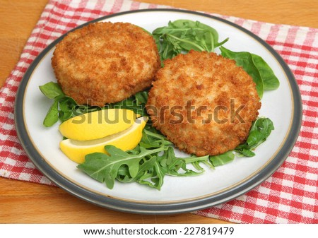Cod fishcakes with rocket, watercress and spinach salad. - stock photo