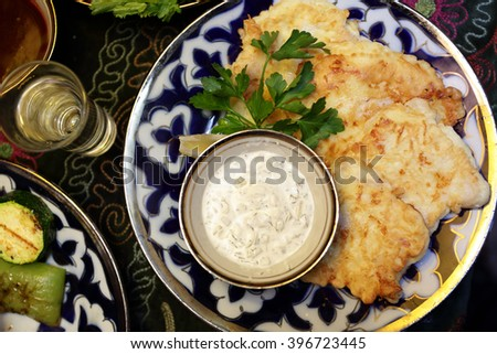 Cod in batter with sauce on a plate in the restaurant - stock photo