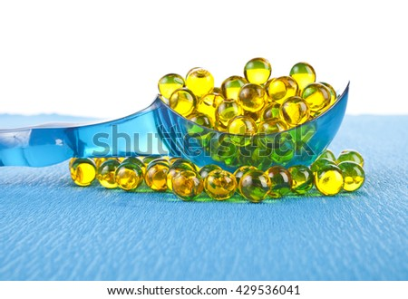 Cod liver oil omega 3 gel capsules in a transparent blue spoon on a blue background - stock photo