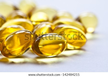 Cod liver oil omega 3 gel capsules isolated on pastel background. Vitamin capsuls - stock photo