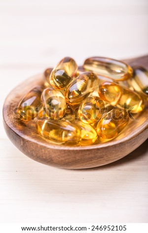 Cod liver oil omega 3 gel capsules isolated on wooden background. Vitamin D capsules. dietary supplement  - stock photo