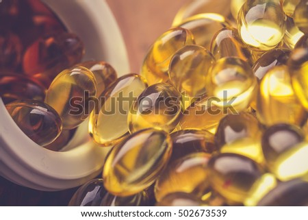 Cod liver oil omega 3 gel capsules isolated on wooden background. Vitamin D capsuls. dietary supplement