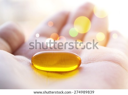 Cod liver oil pill in hand. Magic healing pill. - stock photo