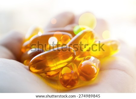 Cod liver oil pills in hand. Magic healing pills. - stock photo