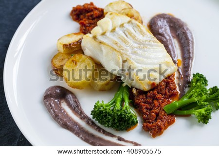 Cod loin with potatoes, black olives puree and sundried tomatoes