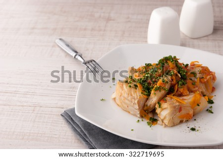Cod with carrot and greens on the ceramic plate with fork  horizontal