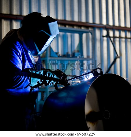 Coded welder in blue overalls busy welding metal parts into a circular vessel with CO² welder - stock photo