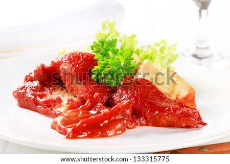 codfish fillet with tomato sauce and lettuce