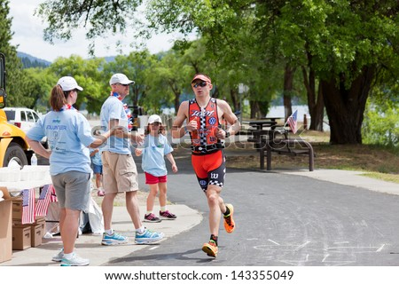COEUR D ALENE, ID - JUNE 23: Ben Hoffman from CO runs past event volunteers at the June 23, 2013 Ironman Triathlon in Coeur d'Alene, Idaho. Ben won the Coeur d'Alene Ironman with a time of 8:17:31. - stock photo
