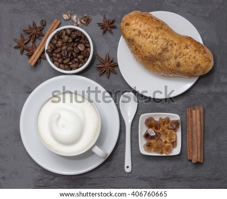Coffe, a cup of hot latte or cappuccino with bun, top view. Background plate made from natural slate. Coffe beans, sugar, cinnamon and decorative star anise for love drink. Coffee shop.  - stock photo