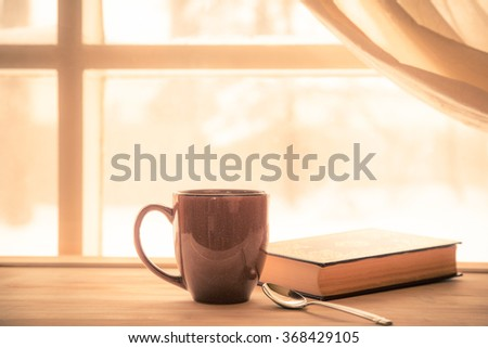 Coffe and Book near window with bright sunny light - stock photo