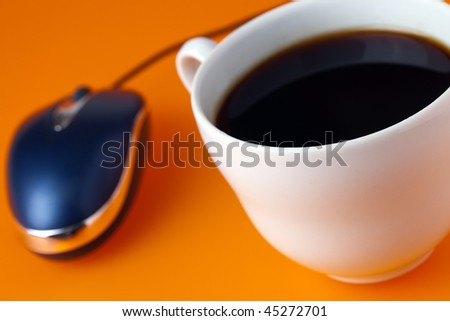 coffe cup and computer mouse on color background - stock photo