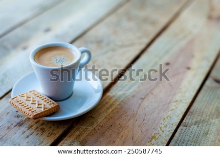 coffe cup and little cookie on a rustic wooden table - stock photo
