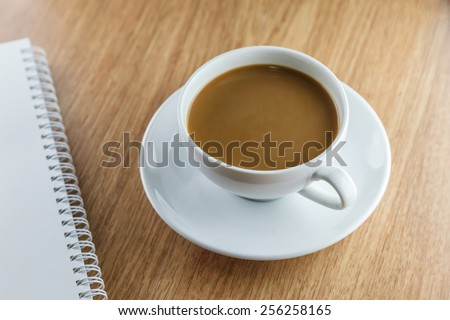 Coffe cup, note book on wooden table