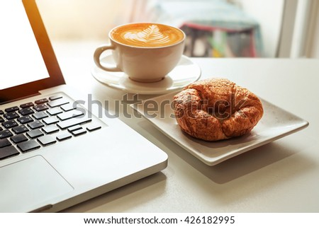 coffe, laptop and croissants to show a business breakfast on the office table in morning  - stock photo