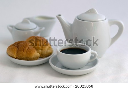 coffe pot, coffecup, two croissant on the plate, milk jug and sugar bowl on white table