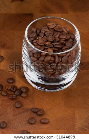 coffea beans in glass on wooden table, black background - stock photo