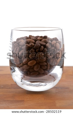 coffea beans in glass on wooden table, white background - stock photo