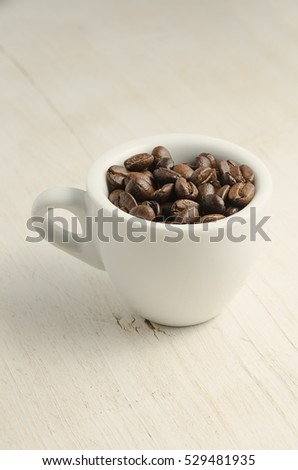 Coffee. A cup and coffee beans on table.