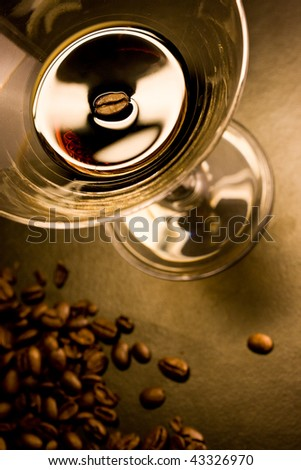 Coffee alcoholic liquor in a martini glass and coffee beans - stock photo