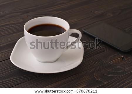 Coffee American with a smartphone on a dark brown table with copy space