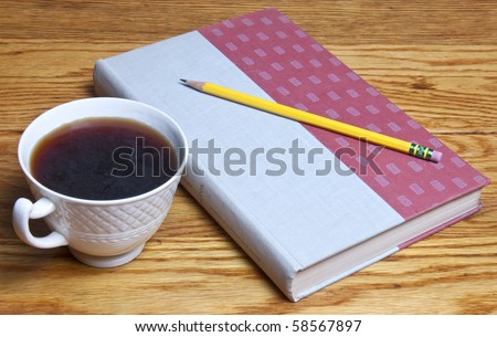 Coffee and a book waiting to be opened, a pencil waiting to take notes, all sitting on a beautiful wood table - stock photo