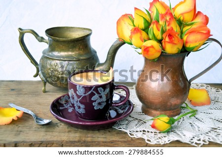 coffee and a bouquet of roses on a wooden background