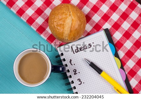 Coffee and a bun on the table next to the notepad. Inventing new ideas for business or life. The concept of motivation and new beginnings. - stock photo