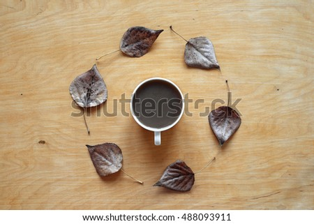 Coffee and autumn leaves on wood