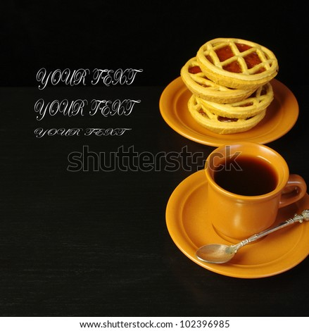Coffee and biscuits on the black table. Your text. Black background