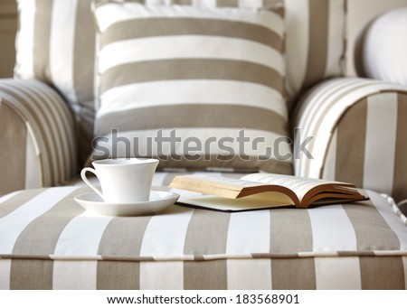 Coffee and book on Sofa with pillow stripe fabric Home Interior decoration - stock photo