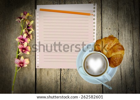 Coffee and bread on wooden table. - stock photo
