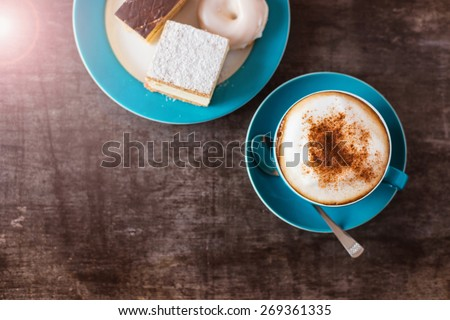 Coffee and cakes on a wooden table background - stock photo