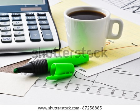 coffee and calculator on paper table with diagram - stock photo
