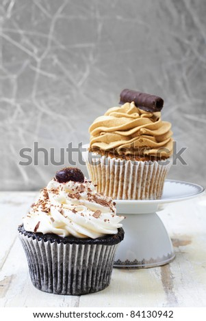 Coffee and chocolate cream and white vanilla cream  cupcakes on a white plate against grunge wooden background, focus on the white cupcake. - stock photo
