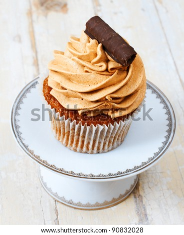 Coffee and chocolate cream cupcake with a swirl on a white plate against grunge wooden background. - stock photo