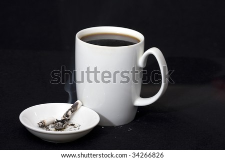 Coffee and cigarette tapped out in ashtray - stock photo
