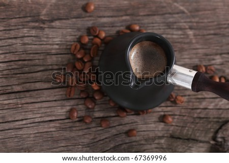 Coffee and coffee beans on the brown woodwn background - stock photo