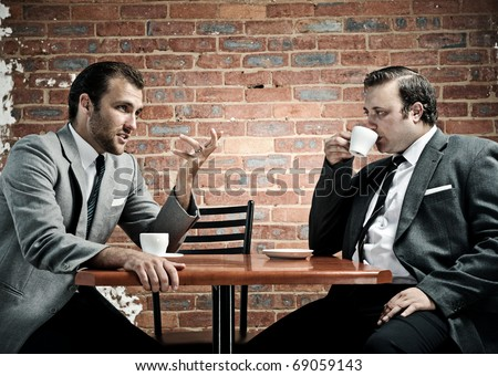 Coffee and conversation between two well dressed men - stock photo