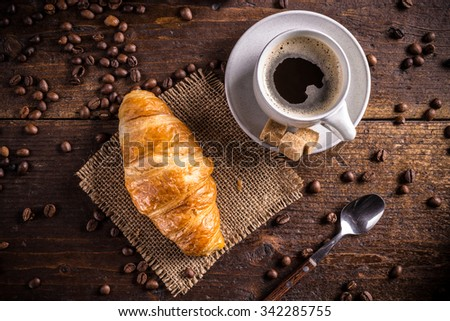 Coffee and croissant on wooden background - stock photo